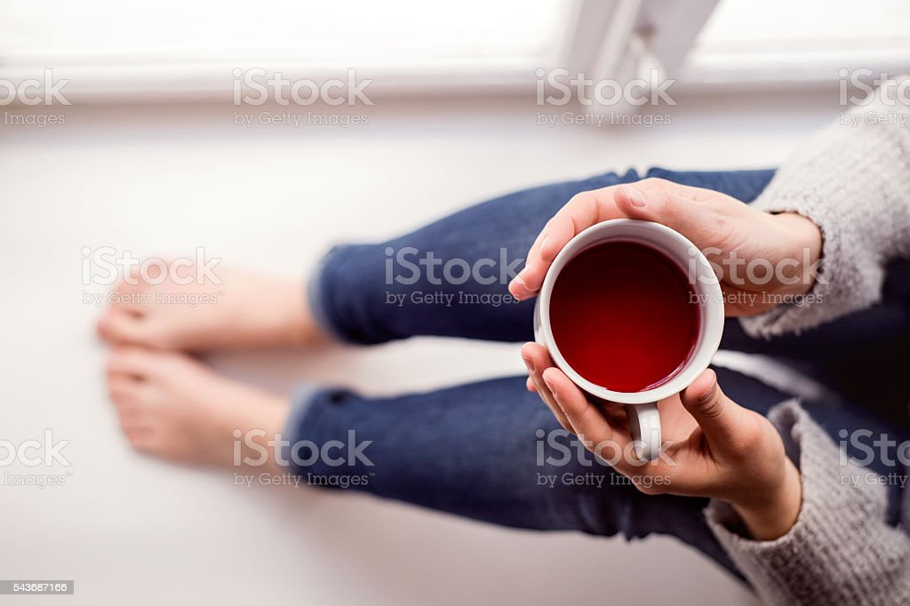 Woman on window sill holding a cup of tea royalty-free stock photo