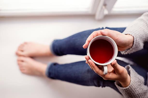 Femme sur Rebord de fenêtre tenant une tasse de thé - Photo
