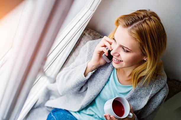 frau auf fensterbank mit smartphone macht anruf - nostalgie telefon stock-fotos und bilder
