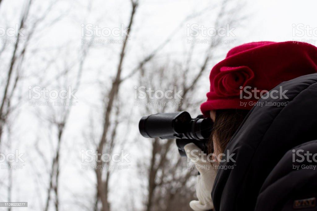 Woman on winter nature hike looking through binoculars stock photo