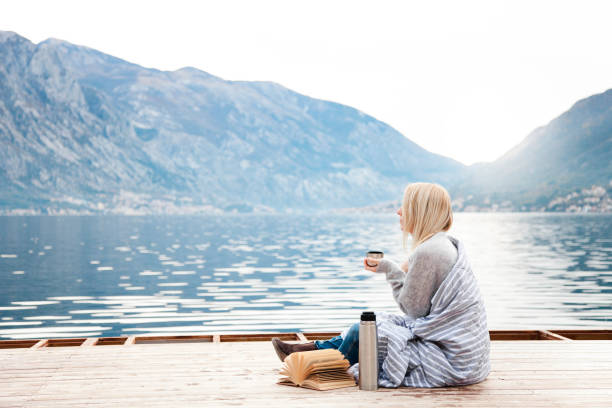 Woman on wooden pier by winter sea, mountains. Cozy picnic with coffee, hot beverages, tea or cocoa stock photo
