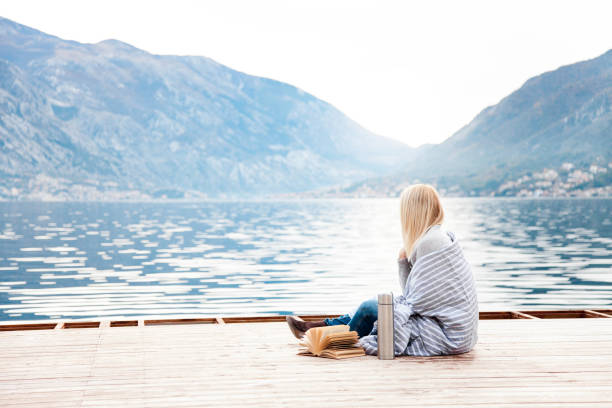 Woman on wooden pier by winter sea, mountains. Cozy picnic with coffee, hot beverages, tea in thermos and mug stock photo