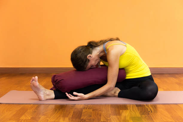 Woman on yellow tank top performing janu sirsasana yoga pose resting forehead on bolster stock photo