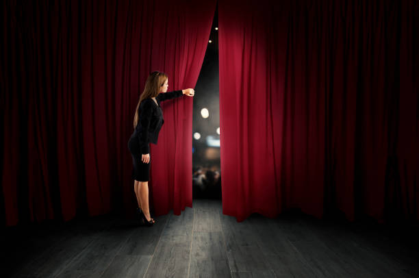 Woman open red curtains of the theater stage - foto stock