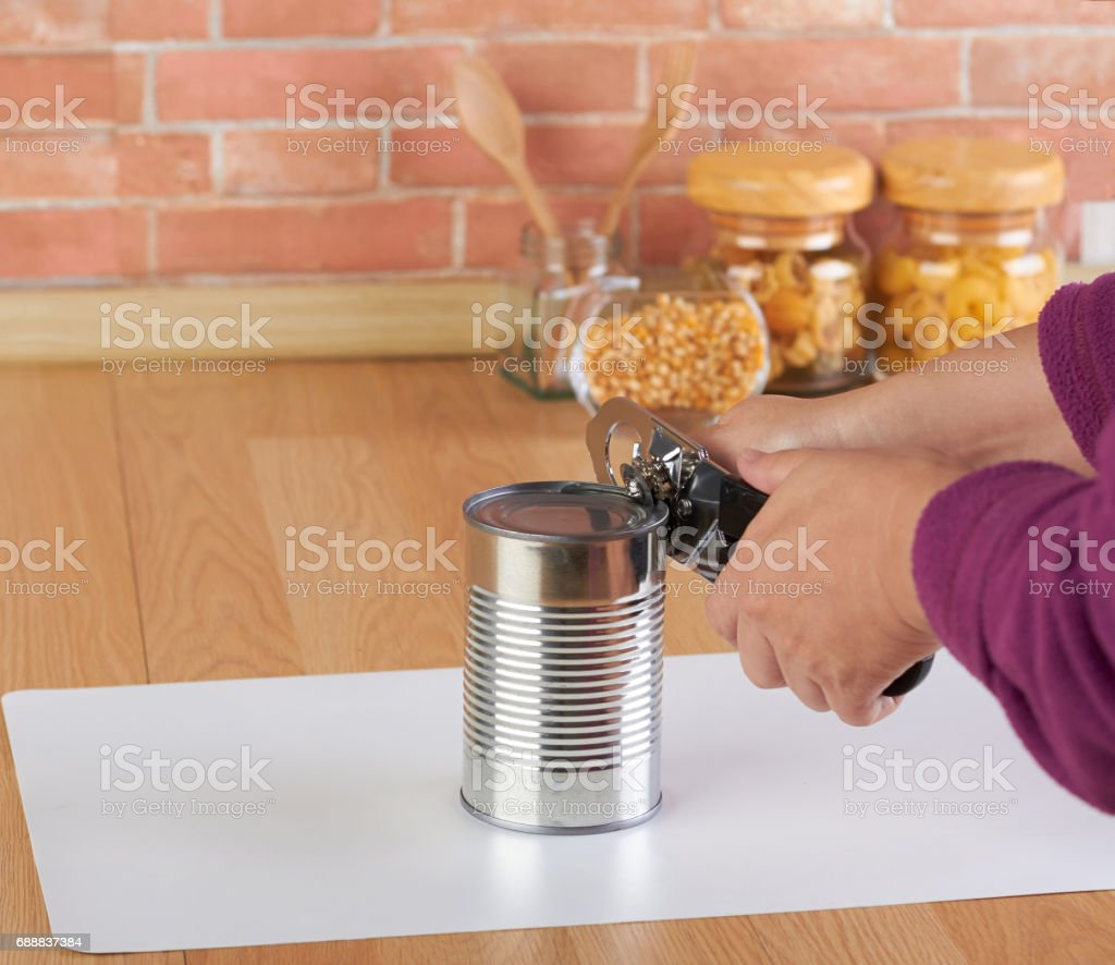 woman opening a can of corn with can opener - foto de stock