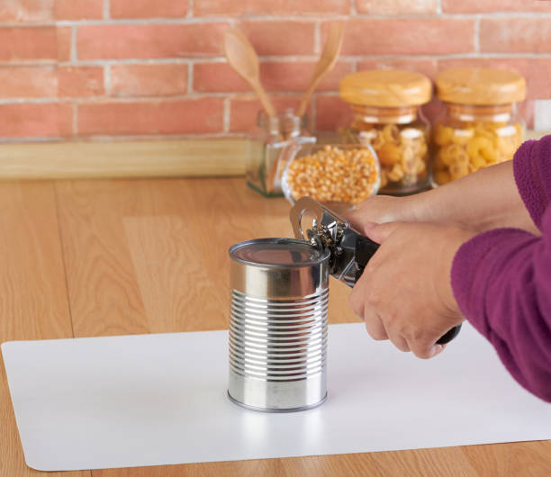 woman opening a can of corn with can opener stock photo