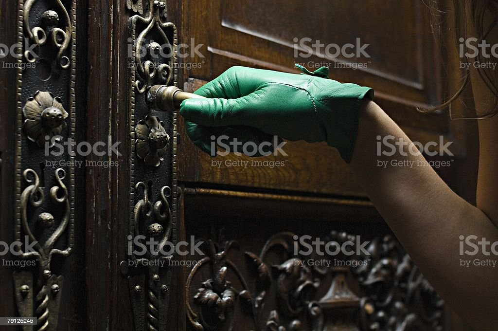 Woman opening a carved wooden door royalty-free 스톡 사진