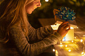 istock Woman opening a gift box. There is a glow coming from the box. 1095621220