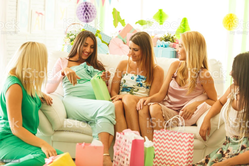 Woman opening baby shower gifts with friends stock photo