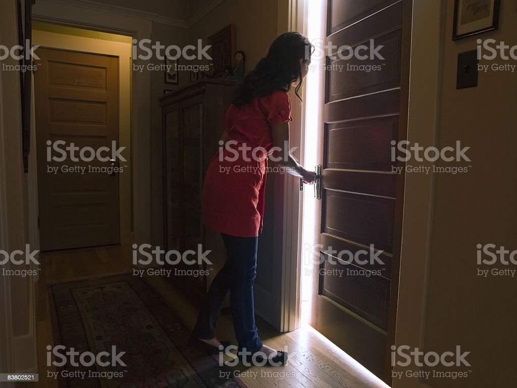 Woman opening bedroom door with light coming out royalty-free stock photo