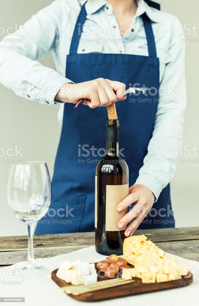 woman opening bottle of white wine stock photo