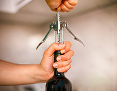 Woman opening bottle of wine with a corkscrew. Close-up