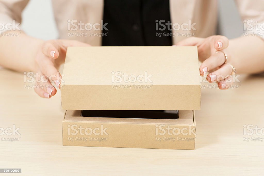 Woman opening box with new parcel, close-up stock photo