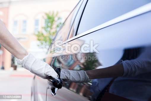 An unrecognizable woman opens a car door while wearing protective gloves.
