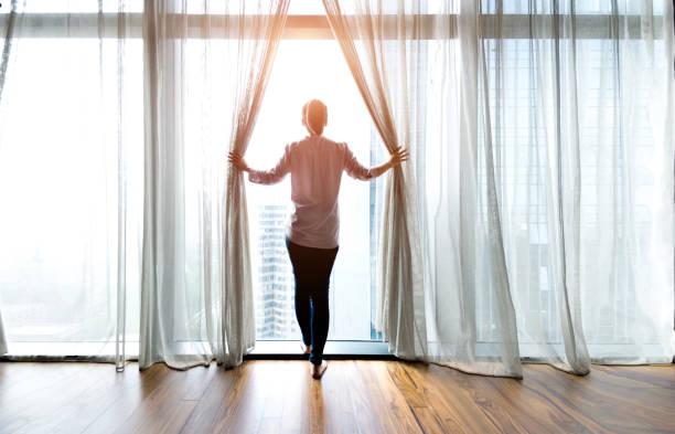 打開窗簾和看著外面的女人 - 明亮 個照片及圖片檔