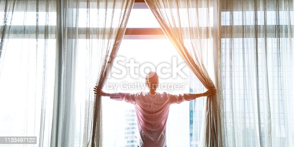949450544istockphoto Woman opening curtains and looking out 1133497122