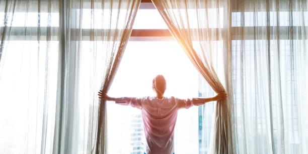 mujer abriendo cortinas y mirando hacia fuera - la mañana fotografías e imágenes de stock