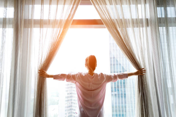 woman opening curtains and looking out - looking at view stock pictures, royalty-free photos & images
