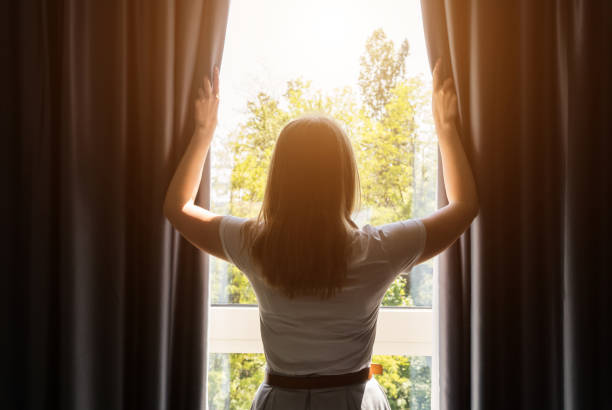 Woman opening curtains in the hotel room at sunny morning. stock photo