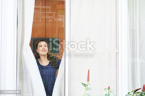 Happy smiling mature Asian woman opening curtains and looking out of window