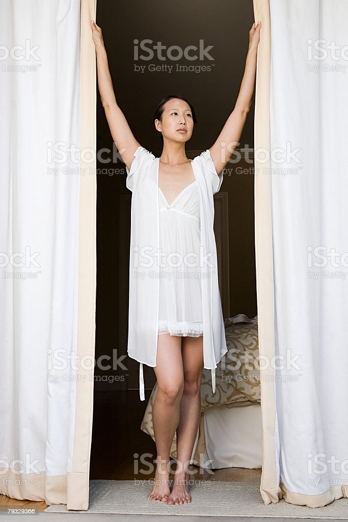 Woman opening curtains stock photo