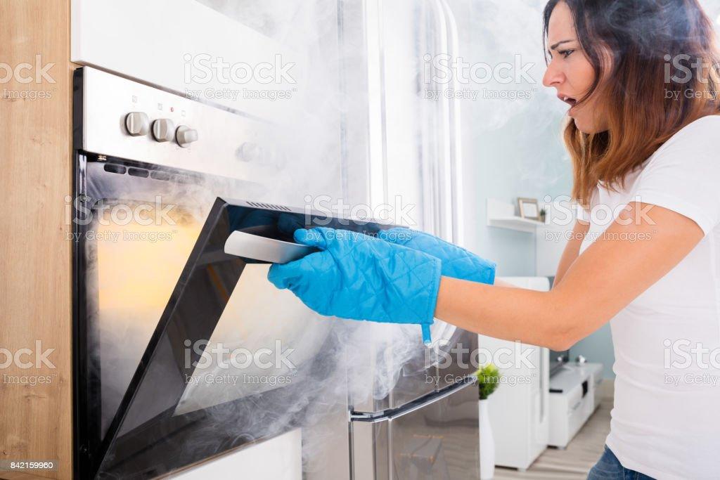 Woman Opening Door Of Oven Full Of Smoke stock photo
