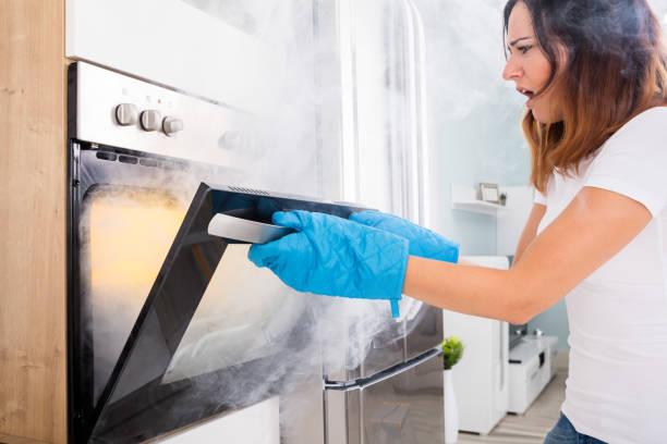 woman opening door of oven full of smoke - burned oven imagens e fotografias de stock