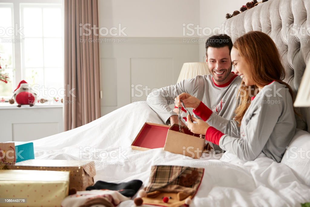 Woman Opening Gift Of Necklace In Bed At Home As Couple Exchange...