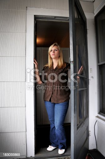 Woman opening the screen door of her apartment. She looks out towards a new arrival approaching her entry. She looks a bit sad/serious.