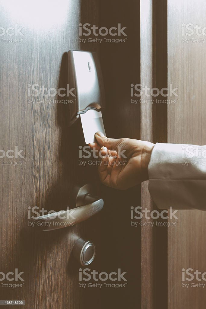 Woman opening hotel room door stock photo