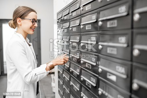 istock Woman opening mailbox at the residential building hall 1065781848