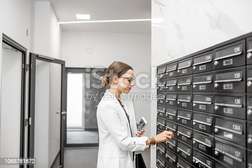 istock Woman opening mailbox at the residential building hall 1065781872