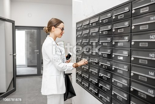 istock Woman opening mailbox at the residential building hall 1065781878