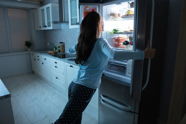 Woman Opening Refrigerator Door Woman Opening Refrigerator Door With Various Food In Kitchen midnight stock pictures, royalty-free photos & images
