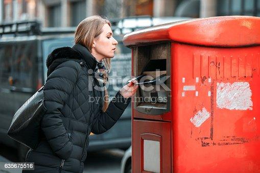 Woman opening street trash bin to dispose of trash