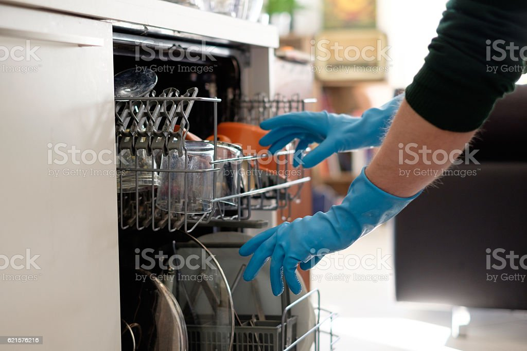Woman opening the dishwasher in the kitchen photo libre de droits