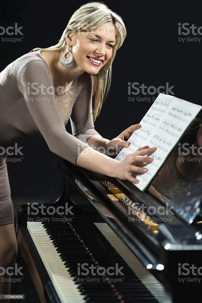 Woman opening the sheet music and preparing to play piano royalty-free stock photo