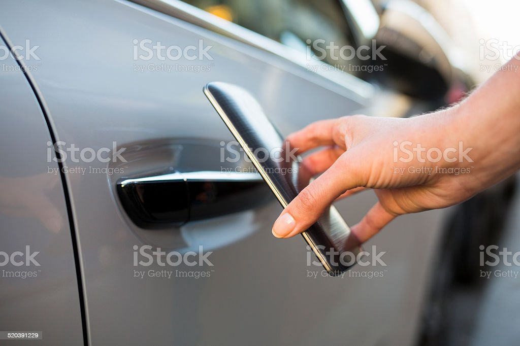 Woman opens her car with her ​​smart phone stock photo