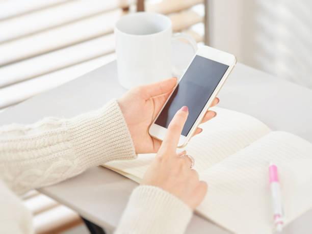 スマートフォンを操作する女性 - 女性 手 ストックフォトと画像