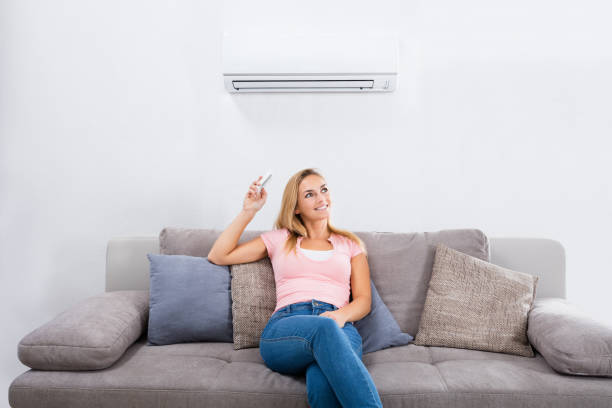 Woman Operating Air Conditioner With Remote Control stock photo