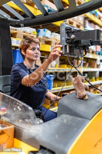 istock Woman operating forklift in warehouse 1056195900