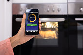 Close-up Of Woman's Hand Operating An Oven Application With Mobile Phone App