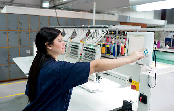 Woman operating the embroidery machine - foto de stock