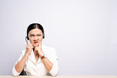 Woman operator in headset feel angry over white background