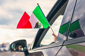 Woman or Girl Holding Mexican Flag from the open car window. Concept