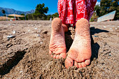 Young girls legs on beach. Summertime relax. Womans or kids feet on beach. Vacation travel concept. Happy people. Banner with copyspace. Stock photo.