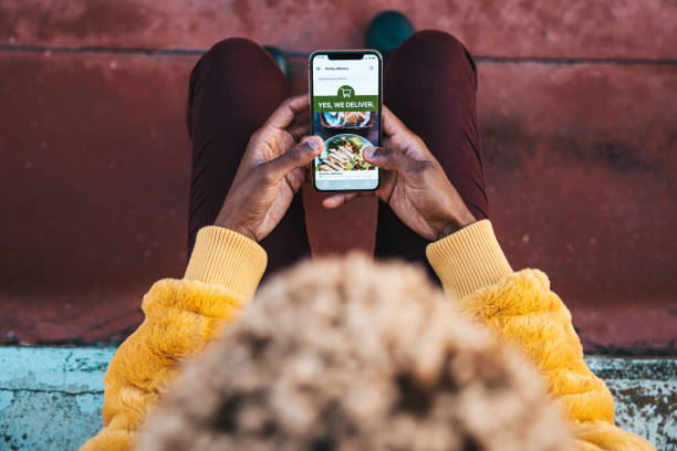 Woman ordering food by delivery mobile app stock photo