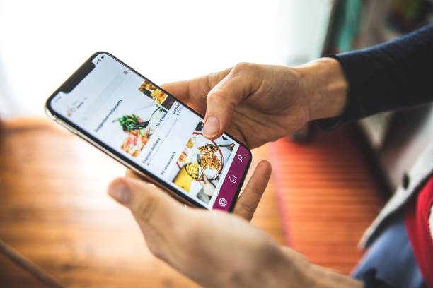 frau bestellt lebensmittel per mobile app lieferung zu hause zur sozialen abstandszeit - bestellen stock-fotos und bilder