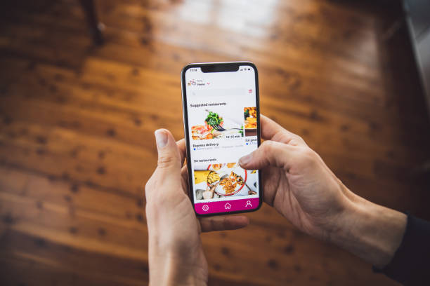 Woman ordering food by mobile app delivery at home at social distancing time stock photo