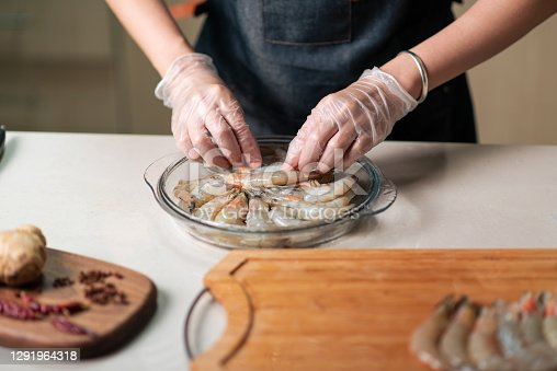 Woman ordering fresh shrimps for cooking in the glass bowl in the kitchen at home